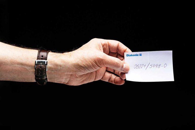 Hand hält Zettel mit Telefonnummer