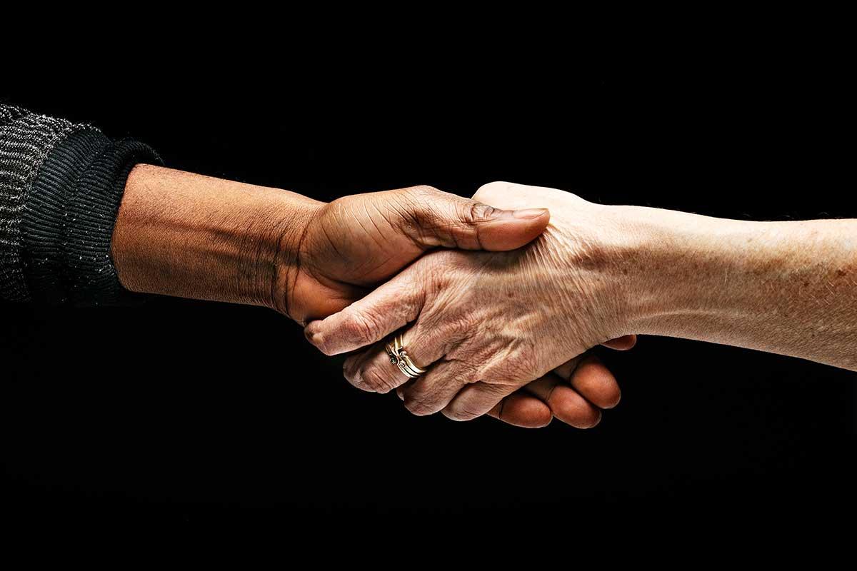 2 Menschen reichen sich die Hände