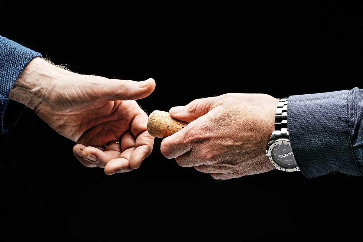 2 Hände überreichen einen Korken