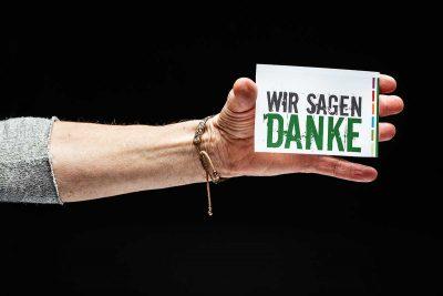 Hand hält Karte mit Aufschrift Wir sagen Danke