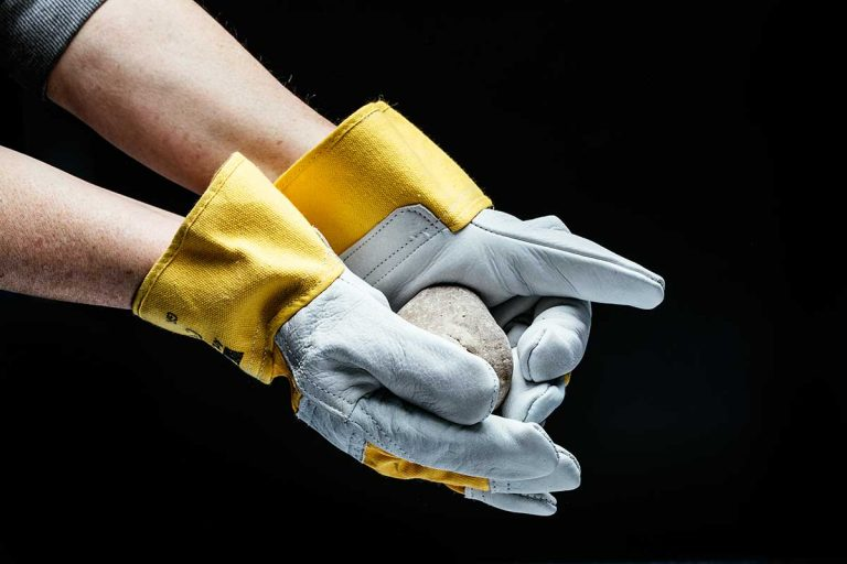 Hände mit Handschuhen halten einen Stein