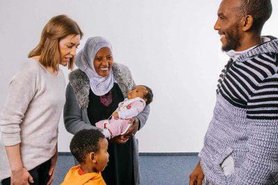 Beraterin steht mit Eltern und 2 Kindern im Beratungsraum